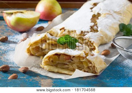Freshly Baked Apple Strudel With Almonds, Decorated With Powdered Sugar And Mint Leaves.