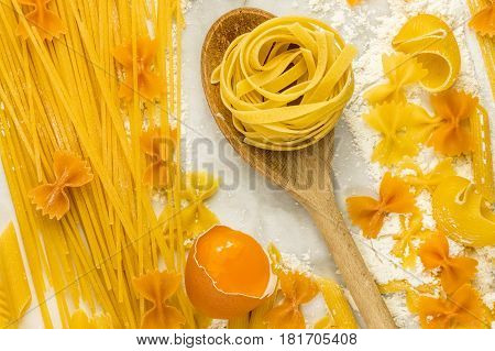 A closeup of various types of pasta on a white marble table with flour and an egg, shot from above