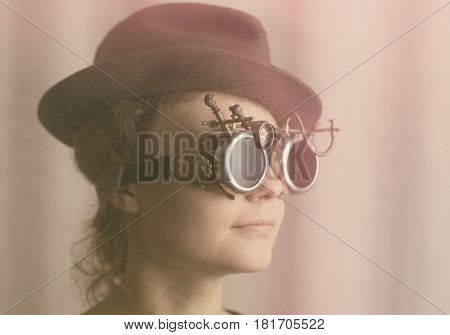 Portrait of attractive steampunk girl wearing googles and hat on light background