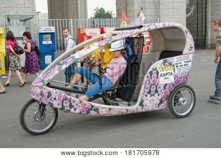 Moscow, Russia - July 3, 2010: Woman on a trishaw expects the passenger on VDNH
