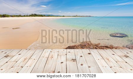 Wood floor on blur beautiful sand and sea scenery background