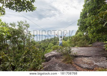 Traveler man standing on big stone holding his hand up and see landscape view at Dragon Crest mountain popular landmark travel adventure in krabi thailand