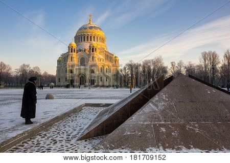 Revolutionary memorial - quenchless flame at Yakornaya square and Orthodox Naval cathedral of Saint Nicholas in Kronshtadt Saint Petersburg Russia poster