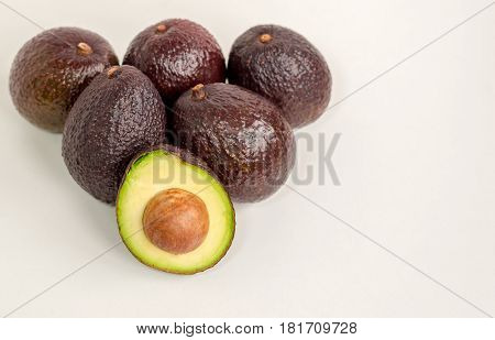 Brown avocado fruit isolated with green half with seed white background