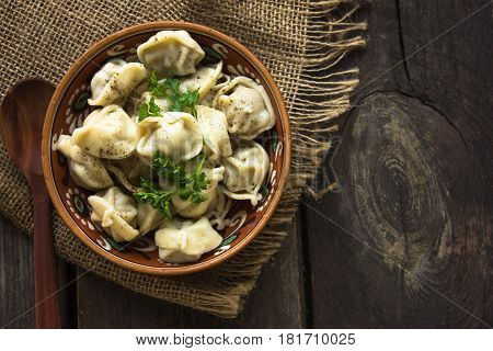 Bowl of dumplings with wood spoon. Russian national food. Dumplings with sour cream and pepper in ceramic bowl on wooden table