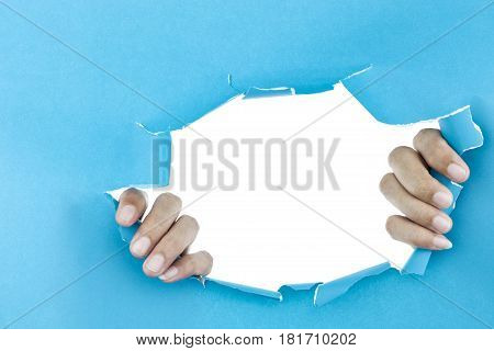 male hand ripped blue paper on white background