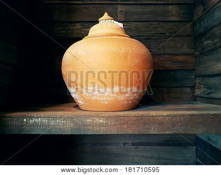 Clay pot on the wooden shelves,The traditional clay pot making in Thailand,abstract photo,vintage.