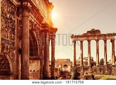 Arch of Emperor Septimius Severus and Temple of Saturn in the distance at the Roman Forum. Rome, Italy.