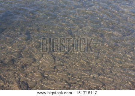 Transparent shallow water with reef rocky bottom fading away to deeper area at top photo