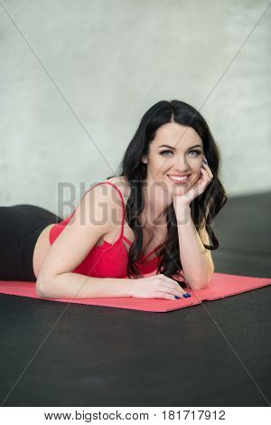 Beautiful girl in a sport suit resting on the mat after the workout