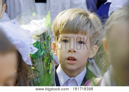 A confused first-grader in a school line with a bouquet of flowers
