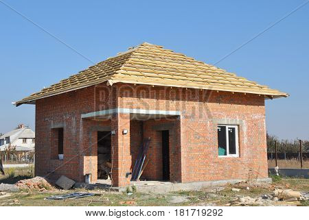 Brick House Construction Site. Roofing Construction. Roof with Wooden Trusses and Insulation Membrane ready to Install Asphalt Shingles. Unfinished house. Building insulation. Roof Repair.