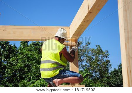 KIEV - UKRAINE APRIL - 20, 2017: Roofer building house roof wooden trusses. Contractor with Hammer Roofing Construction. Roofer Construction. Roof repair.