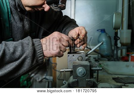 Mechanics repairing a diesel injector. Man disassemble a injector pinched in a vise.