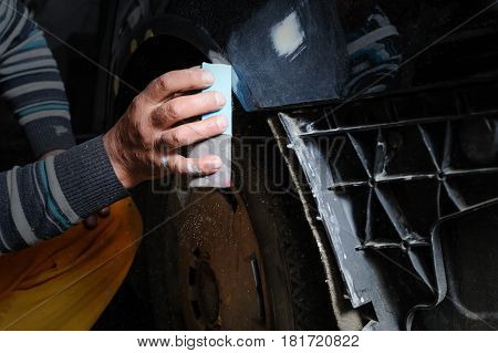 Car body repair. A fitter is fixing a dents on a car. Man's hand is polishing a surface after puttying.