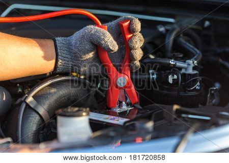 Hand Of Car Technician Holding Cable To Connect To Battery