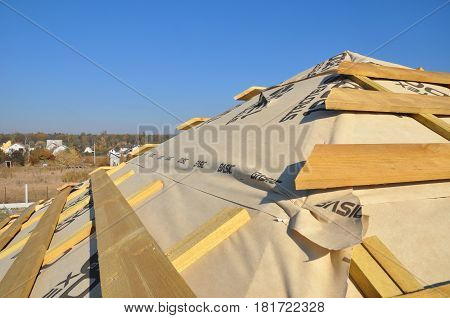 KIEV - UKRAINE APRIL - 24, 2017:  Roofing Construction. Install House Roof with wooden trusses and Insulation Membrane. Asphalt Shingles.