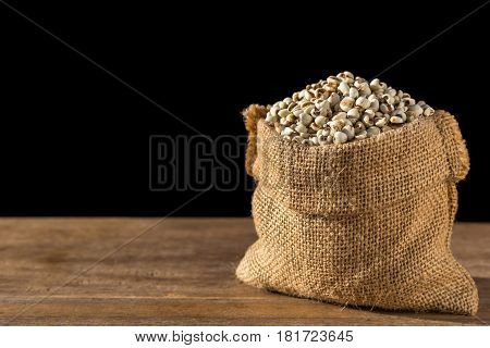 Millet Rice Or Millet Grains In Small Sack On Wooden Table. Isolated On Black Background