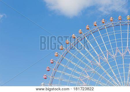 Big funfair festival wheel against blue sky background