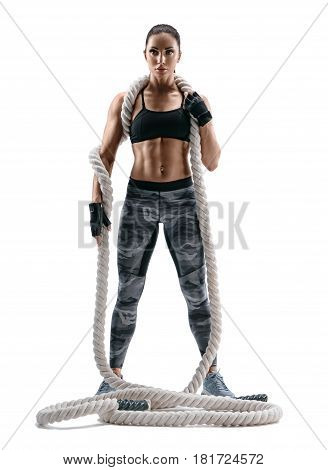 Attractive strong woman with heavy ropes on her shoulders. Photo of young brunette in sportswear isolated on white background. Strength and motivation.