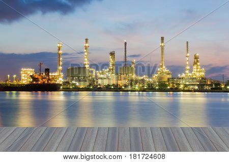 Opeing wooden floor Petrol refinery plant water front with twilight sky background