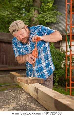 Carpenter working by hand drill on natural background