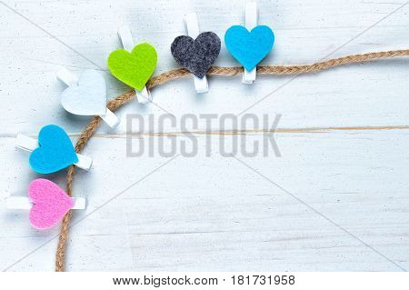 Colorful hearts on a twine on old white natural wooden background. Flat lay top view. Copy space on the bottom right.