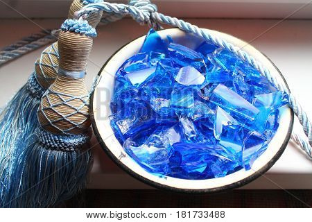 fragments of broken glass blue color use for decoration