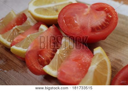 slices of ripe red tomato and sour yellow lemon prepare for cook and decoration