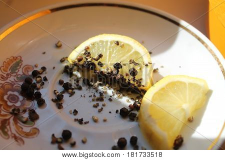 juicy slices of sour yellow lemon with grains of black pepper lay on plate