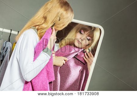 Pretty happy woman watching at her into mirror in clothing from new collection wardrobe. Young undecided shopper girl choosing in second hand. Shopping sale concept.