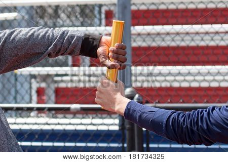 Two runners exchange the baton at practice