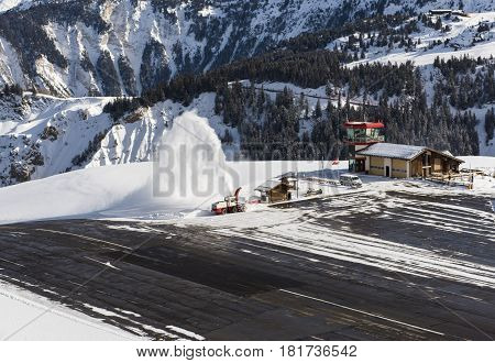 Small airport altiport runway being cleared of snow by blower on the side of an alpine mountain in winter