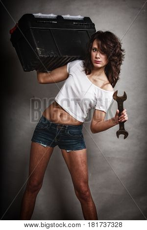 Sex equality and feminism. Sexy girl holding toolbox and wrench spanner on gray. Young attractive woman working as construction worker. Studio shot.