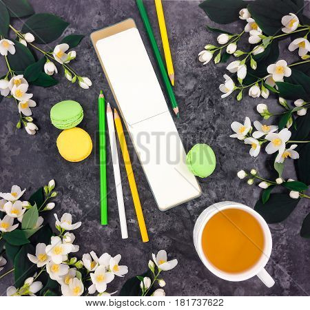 Spring bright composition of cup of green tea macarons open empty sketchbook with pencils and jasmine flowers on vintage stone marble table. Flat lay top view