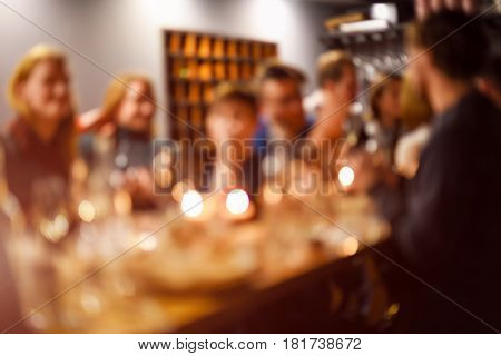 Abstract blurred group of friends meeting in the restaurant. Blurry background of caucasian people having fun, eating and celedrating together. Lifestyle, friendship, party concept.