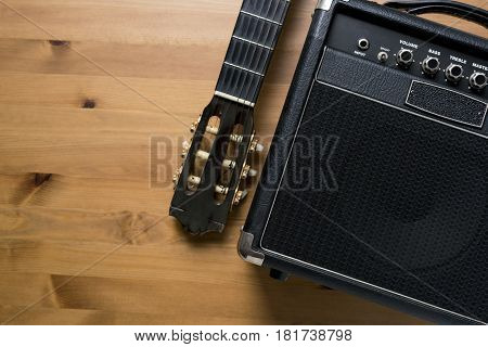 Guitar amplifier and old classical guitar on wood table