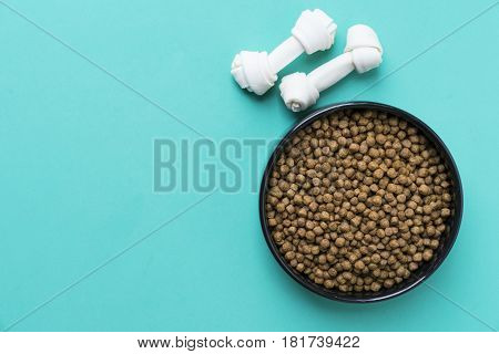 Dog bones and dog food on green background