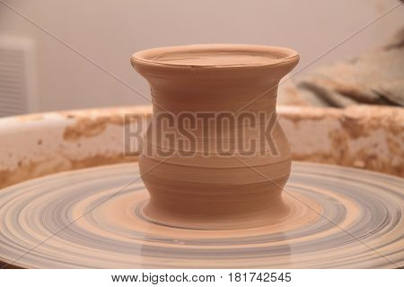 Clay pot on a pottery wheel, pottery craft, moulding the pot with your hands, sculpting hands