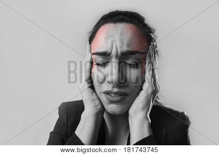 black and white close up face of young business woman in office suit suffering migraine pain and strong headache with fingers on her tempo in business stress and work problem isolated background