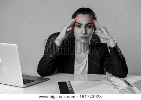 young attractive business woman working at laptop computer office desk in stress suffering intense headache and migraine feeling overworked and overwhelmed in work crisis concept