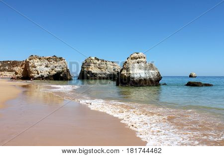 Portugal Algarve Portimao. Rocks in the atlantic ocean and wave on blue sky background horizontal view