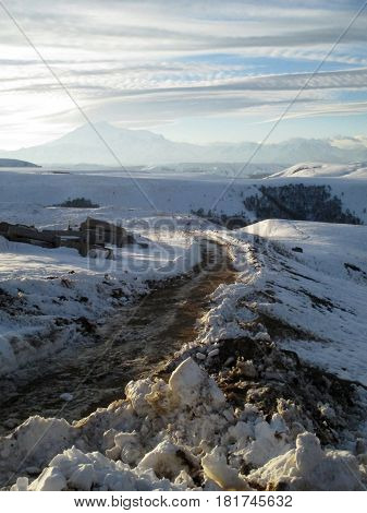 Russia Caucasia. Road and snow on mountain and blue sky background vertical view