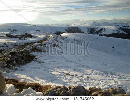 Russia Caucasia. Road and snow on mountain and blue sky background horizontal view