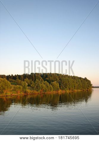 Green autumnal forest near river on blue sky background vertical view