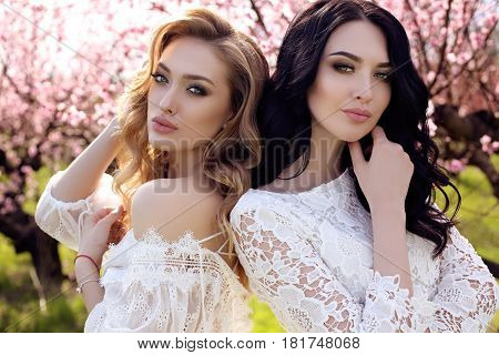 Gorgeous Young Women In Elegant Dress Posing In Garden With Blossom Peach Trees