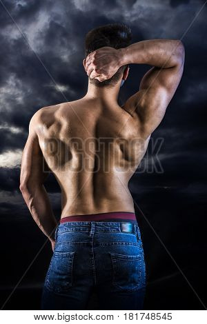Back of young muscular man shirtless wearing jeans, against night cloudy sky, looking in the distance