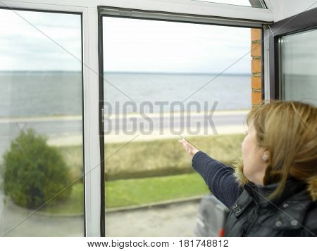 Woman pointing her hand to the sea and sky standing near open window. Particular focus cropped shot