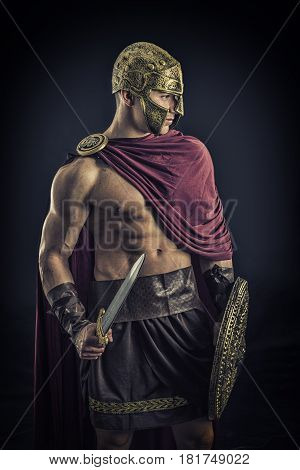 Young handsome muscular man posing in roman or spartan gladiator costume with shield and sword, on black background in studio