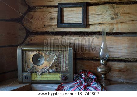 Old vintage household items in the old rural abandoned house. Wooden bench an old kerosene lamp and frame photo on the log wall women's shawl. Old radio. Still life